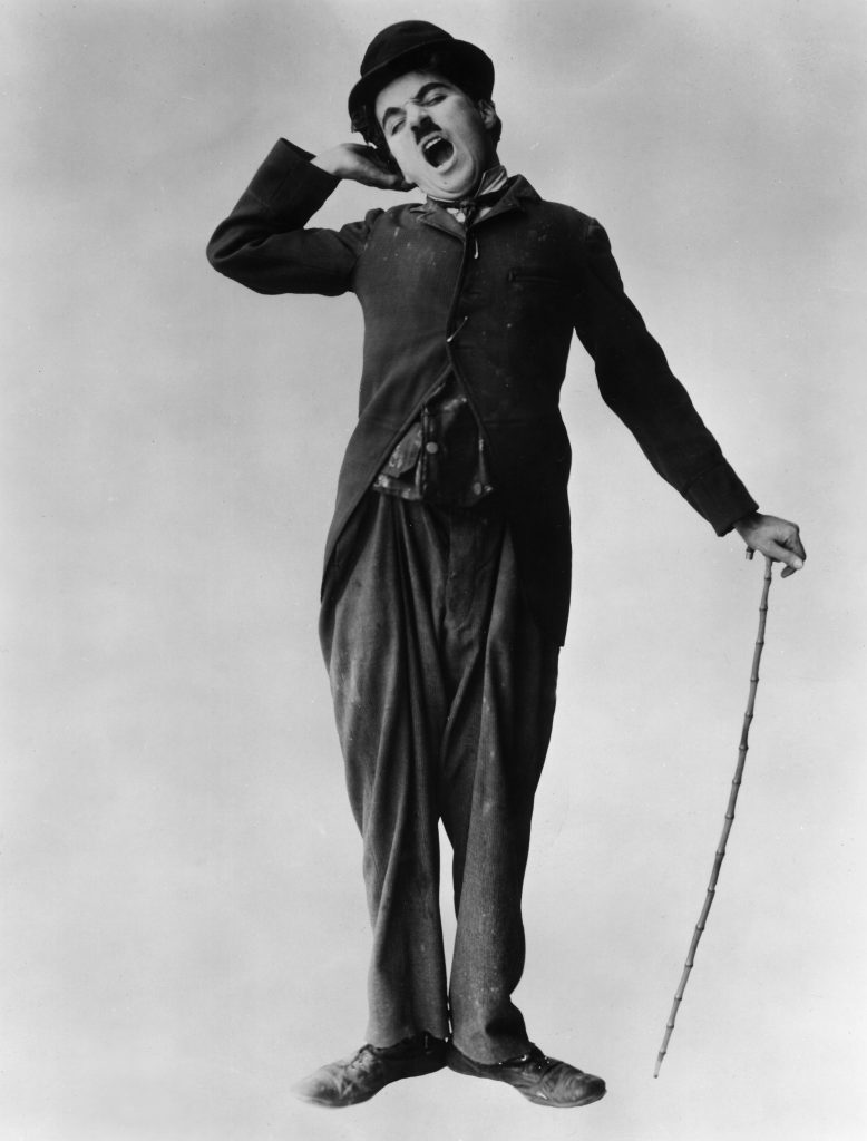 1915: British actor and director Charlie Chaplin (1889 - 1977) stretches and yawns in a full-length promotional portrait for his film 'The Tramp'. (Photo by Hulton Archive/Getty Images)